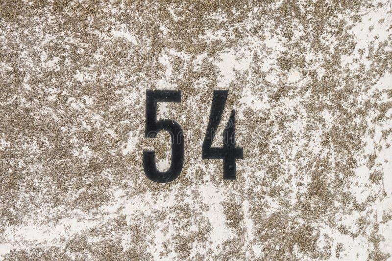 O número 54, cinquenta e quatro, em uma superfície com líquene foto de stock