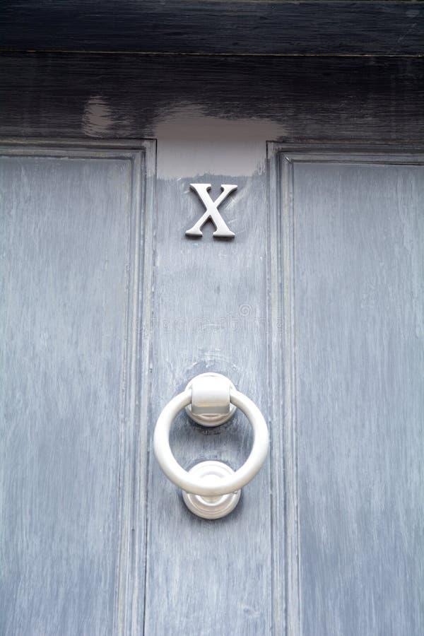 O número da casa 10 mostrado como o numeral romano X no azul pintou a porta imagem de stock royalty free