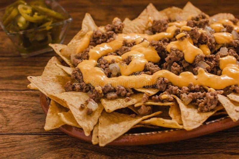 O Nacho lasca o milho com carne picada, queijo derretido, jalapeños na placa no alimento picante mexicano da tabela de madeira e imagem de stock royalty free