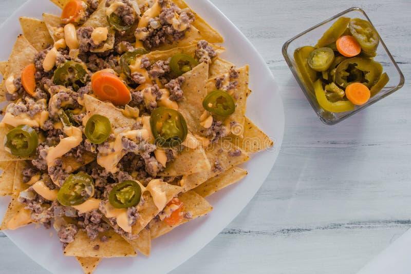 O Nacho lasca o milho decorado com carne picada, queijo derretido, alimento picante mexicano das pimentas dos jalapenos em México imagem de stock