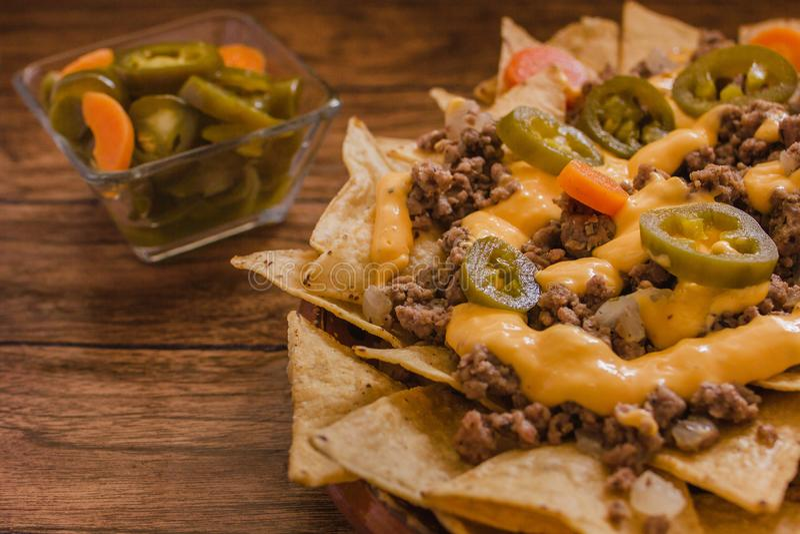 O Nacho lasca o milho decorado com carne picada, queijo derretido, pimentas dos jalapeños, alimento picante mexicano em mexic imagens de stock royalty free