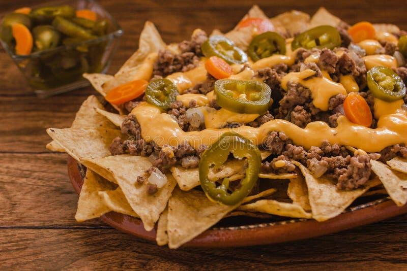 O Nacho lasca o milho decorado com carne picada, queijo derretido, pimentas dos jalapenos no alimento picante mexicano da placa e foto de stock royalty free