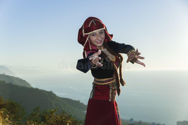 O nacional georgian de dança da jovem mulher veste o verão das montanhas fora ensolarado imagens de stock royalty free