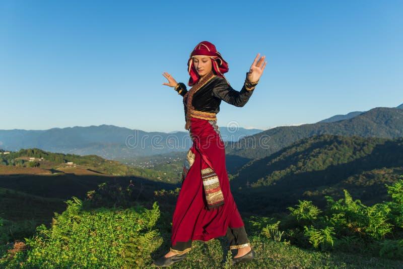 O nacional georgian de dança da jovem mulher veste o verão das montanhas fora ensolarado fotos de stock