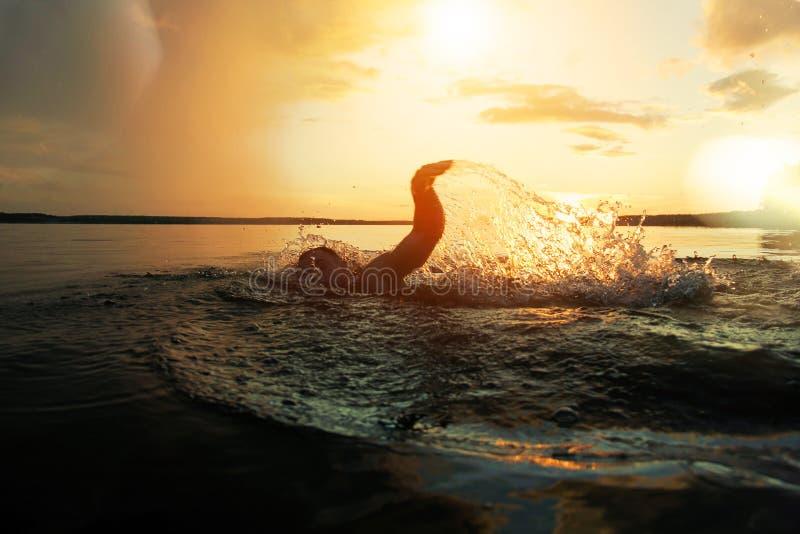 O nadador conduz o treinamento em um lago no por do sol após a chuva De debaixo das mãos voe o pulverizador imagem de stock