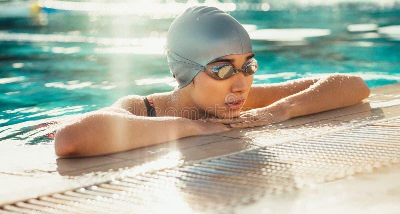 O nadador que toma o resto após pratica foto de stock