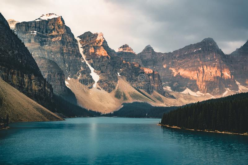 O nascer do sol com águas de turquesa do lago moraine com pecado iluminou montanhas rochosas no parque nacional de Banff de Canad fotografia de stock