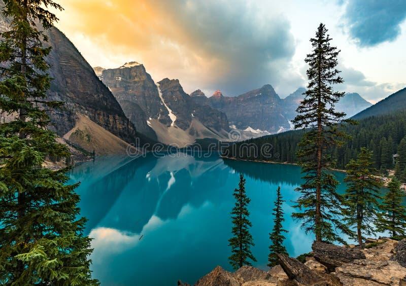 O nascer do sol com águas de turquesa do lago moraine com pecado iluminou montanhas rochosas no parque nacional de Banff de Canad foto de stock royalty free