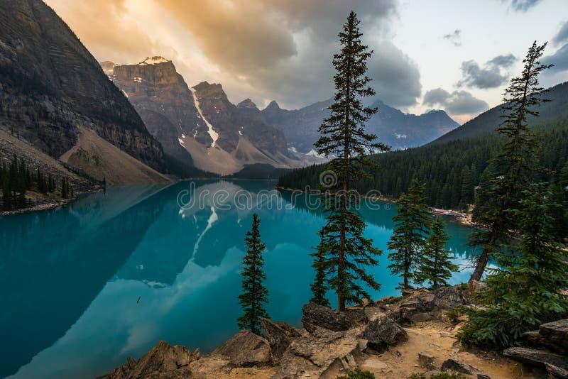 O nascer do sol com águas de turquesa do lago moraine com pecado iluminou montanhas rochosas no parque nacional de Banff de Canad foto de stock
