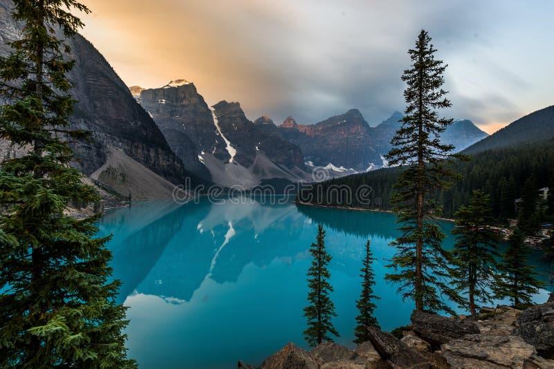O nascer do sol com águas de turquesa do lago moraine com pecado iluminou montanhas rochosas no parque nacional de Banff de Canad imagens de stock royalty free