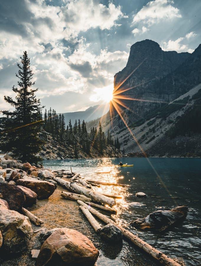 O nascer do sol com águas de turquesa do lago moraine com pecado iluminou montanhas rochosas no parque nacional de Banff de Canad fotografia de stock royalty free