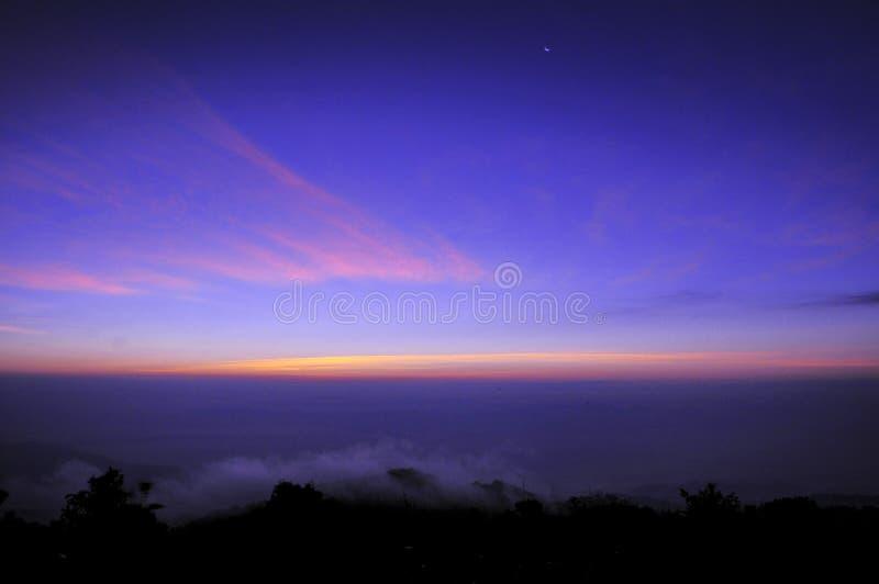 O nascer do sol e a lua caem nas montanhas imagens de stock royalty free