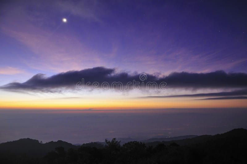 O nascer do sol e a lua caem nas montanhas fotos de stock