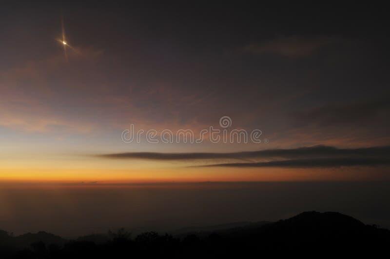 O nascer do sol e a lua caem nas montanhas foto de stock royalty free