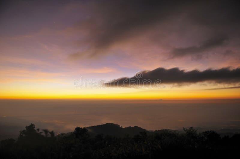 O nascer do sol e a lua caem nas montanhas imagem de stock royalty free