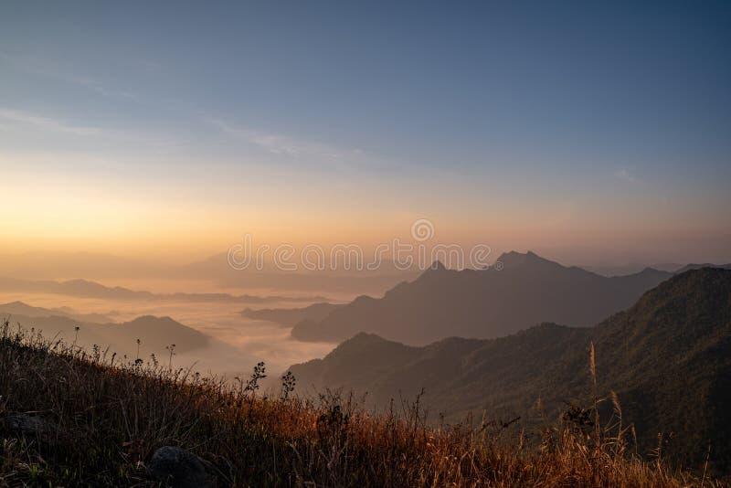 O nascer do sol na montanha com a névoa e a nebulosidade ele fotografia de stock royalty free
