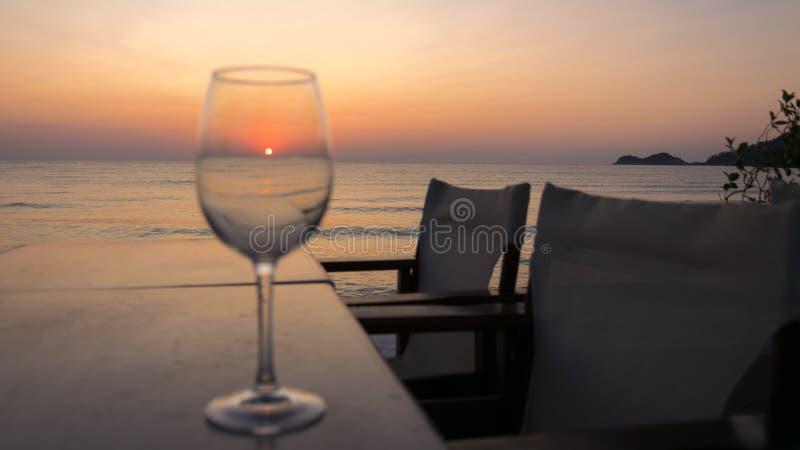O nascer do sol visto completamente um vidro na tabela, com cadeiras e água do mar calma imagens de stock royalty free