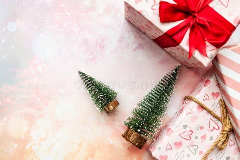 O Natal apresenta com as árvores na configuração lisa da opinião superior do fundo do rosa imagens de stock royalty free