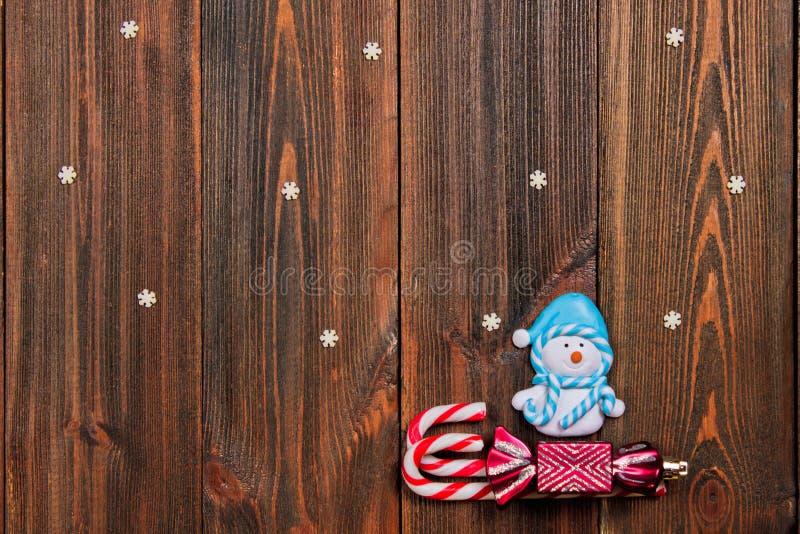 O Natal brinca o boneco de neve em um trenó dos bastões em Ta de madeira marrom imagem de stock royalty free