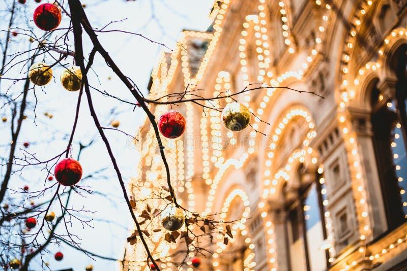 O Natal brinca em um ramo de árvore com luzes do fundo foto de stock royalty free