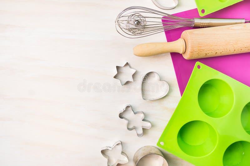 O Natal coze ferramentas para o molde da cookie e do bolo para o queque e o queque no fundo de madeira branco, vista superior foto de stock