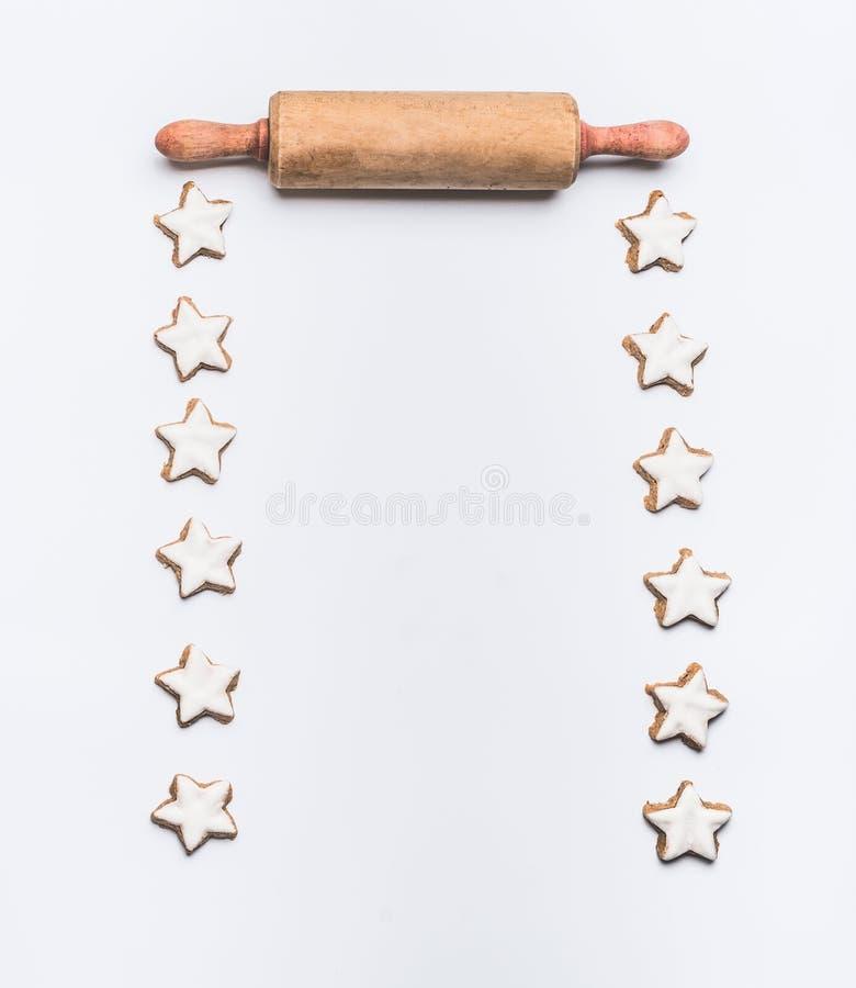 O Natal coze o fundo com as cookies da estrela da canela e o pino do rolo na vista branca, superior foto de stock