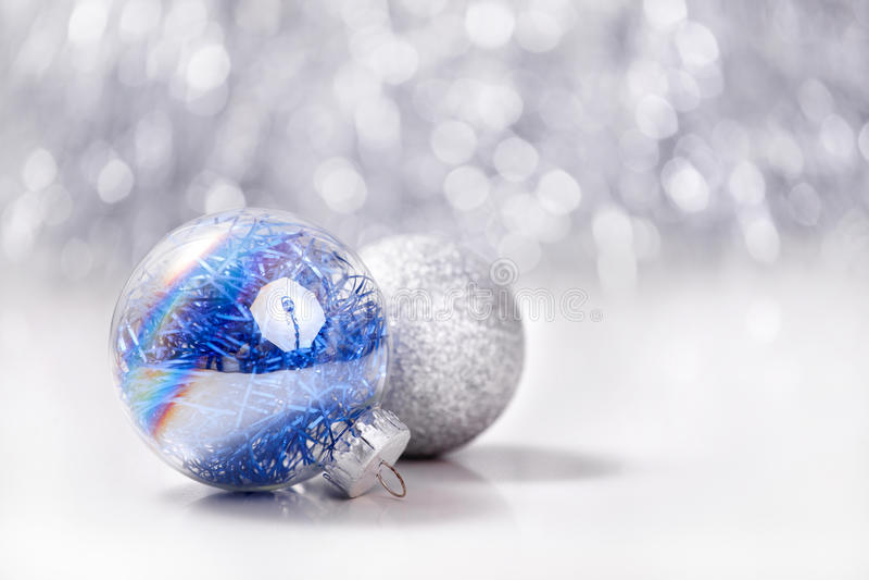 O Natal de prata e azul ornaments bolas no fundo do bokeh do brilho com espaço para o texto Xmas e ano novo feliz fotos de stock royalty free