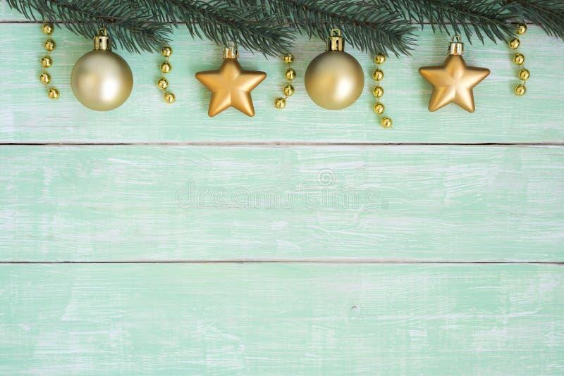 O Natal do ouro ornaments a suspensão no ramo do abeto sobre o vintag verde imagem de stock royalty free
