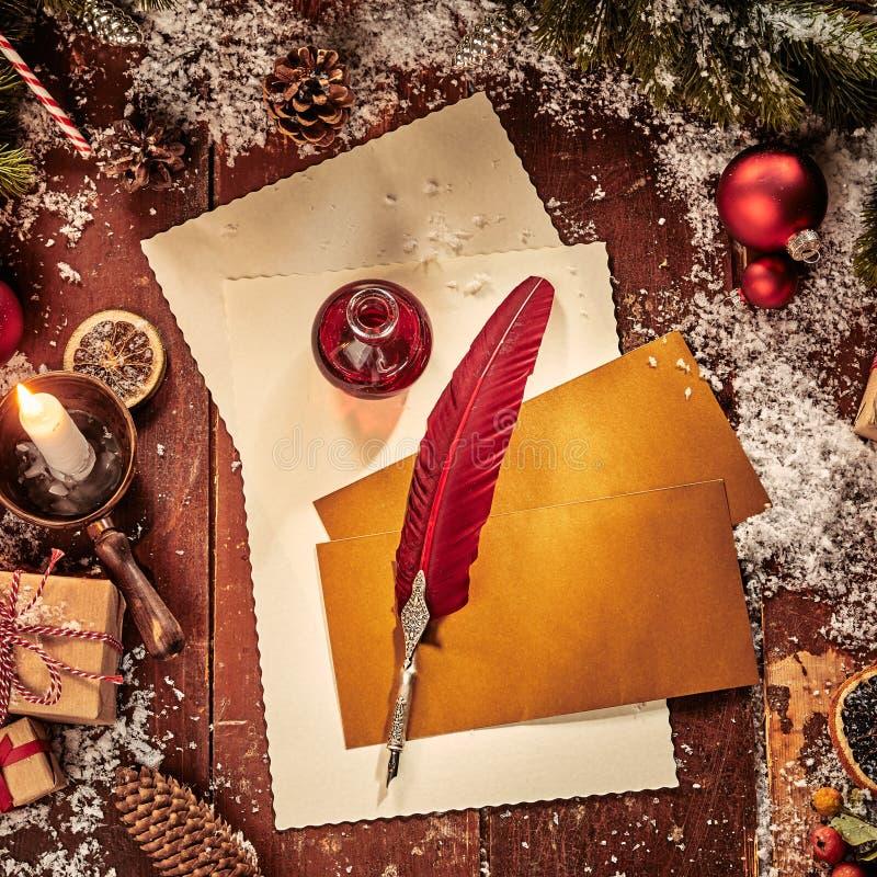O Natal do vintage coloca horizontalmente ainda o fundo da vida com o papel e a pena vermelha da pena cercados pela folha do pinh fotos de stock