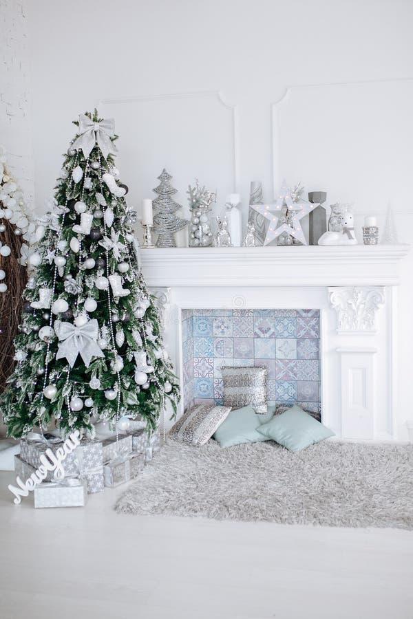 O Natal e o ano novo decoraram a sala interior branca com presentes e árvore e chaminé do ano novo imagem de stock