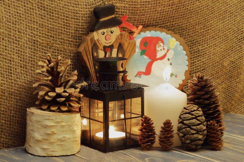 O Natal está vindo Velas iluminadas, lanterna preta do metal, cones de abeto, vassoura de madeira da chaminé e boneco de neve no  fotos de stock royalty free