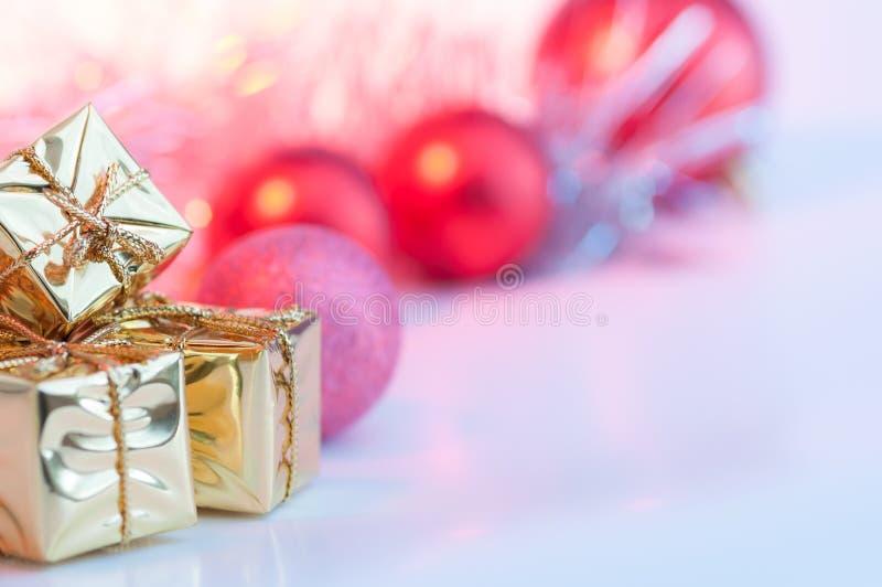 O Natal feliz, ano novo, presentes em umas caixas do ouro, bolas vermelhas do Natal é empilhado no canto esquerdo O fundo é cor-d imagens de stock royalty free