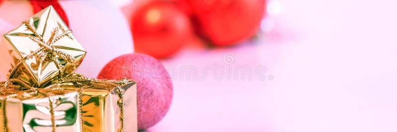 O Natal feliz, ano novo, presentes em umas caixas do ouro, bolas vermelhas do Natal é empilhado no canto esquerdo O fundo é cor-d fotografia de stock