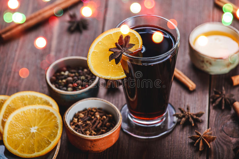 O Natal ferventou com especiarias o vinho com canela, estrelas do anis, mel e fatias alaranjadas no fundo de madeira fotos de stock royalty free