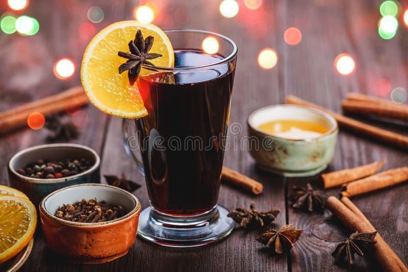 O Natal ferventou com especiarias o vinho com canela, estrelas do anis, mel e fatias alaranjadas no fundo de madeira fotografia de stock
