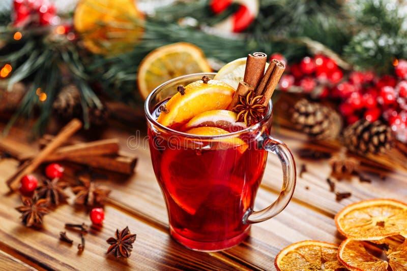 O Natal ferventou com especiarias o vinho tinto com especiarias e frutos em uma tabela r?stica de madeira Bebida quente tradicion foto de stock royalty free