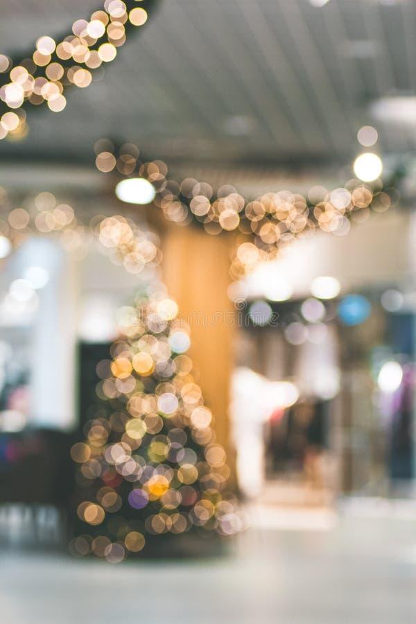 O Natal três com bokeh macio ilumina-se no shopping borrado fora do fundo do foco imagens de stock royalty free