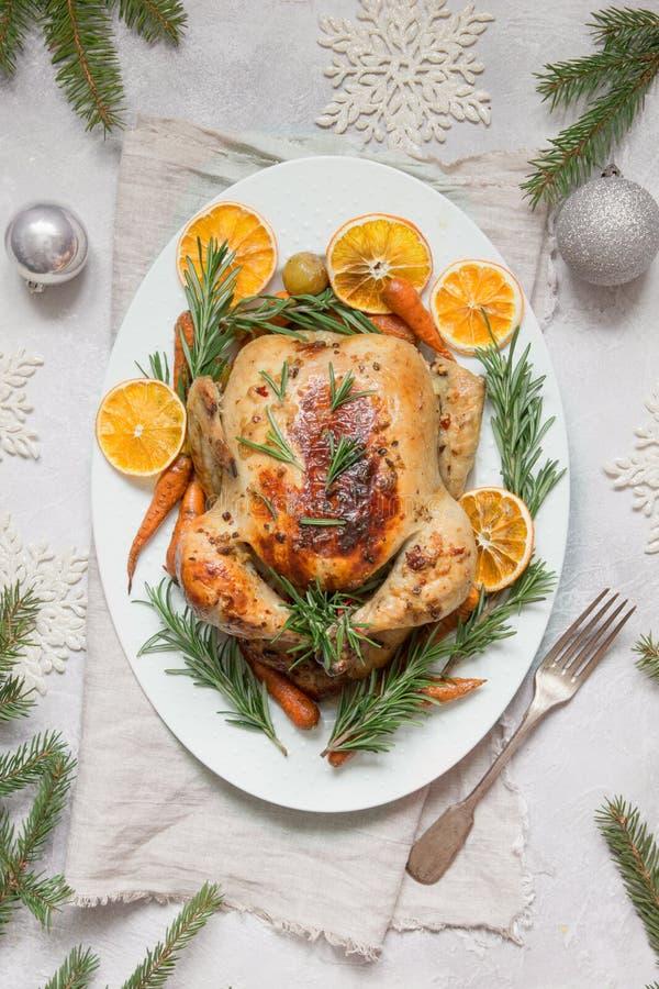 O Natal tradicional roasted a laranja, a cenoura, e os alecrins da guarnição da galinha na tabela clara Vista superior Copie o es fotografia de stock royalty free