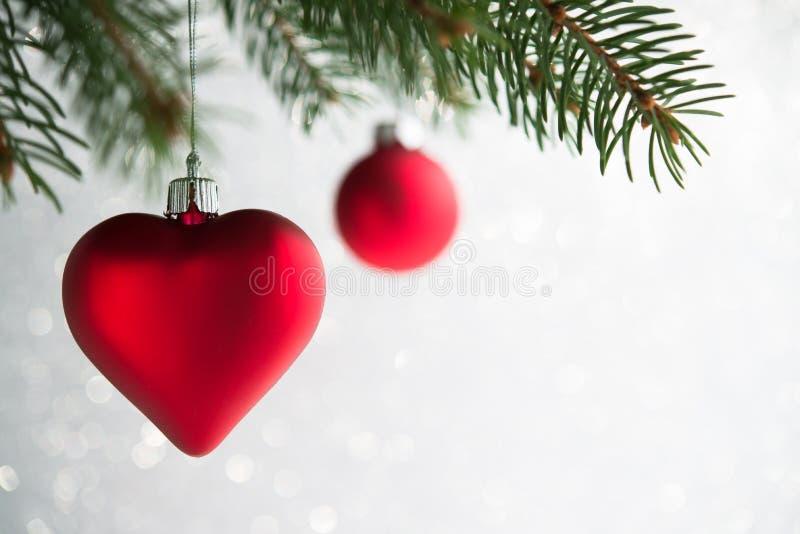 O Natal vermelho ornaments o coração e a bola na árvore do xmas no fundo do bokeh do brilho foto de stock royalty free