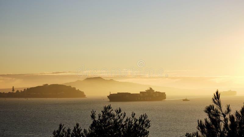 O navio de carga está indo no porto de Auckland no nascer do sol imagens de stock royalty free