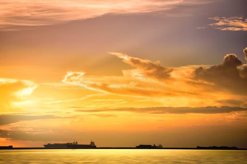 O navio de carga flutua no oceano no tempo do por do sol imagens de stock