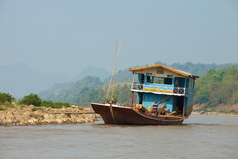 O navio de carga transporta os logs de madeira da teca por Mekong River na estação seca em Luang Prabang, Laos fotografia de stock royalty free