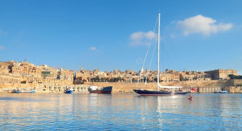 O navio de navigação entra na baía grande em um dia brilhante, panorama de valletta imagem de stock