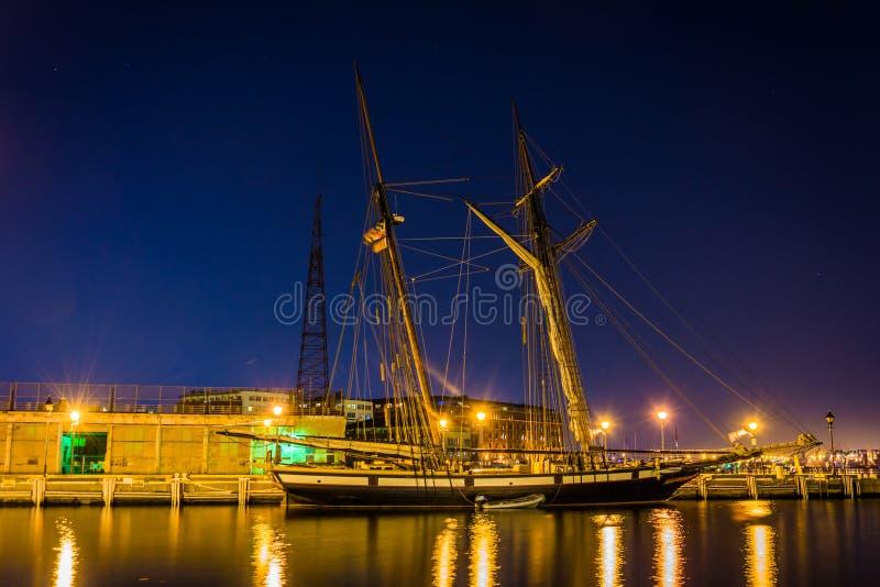 O navio de navigação na margem abate dentro o ponto na noite, Baltimor imagens de stock