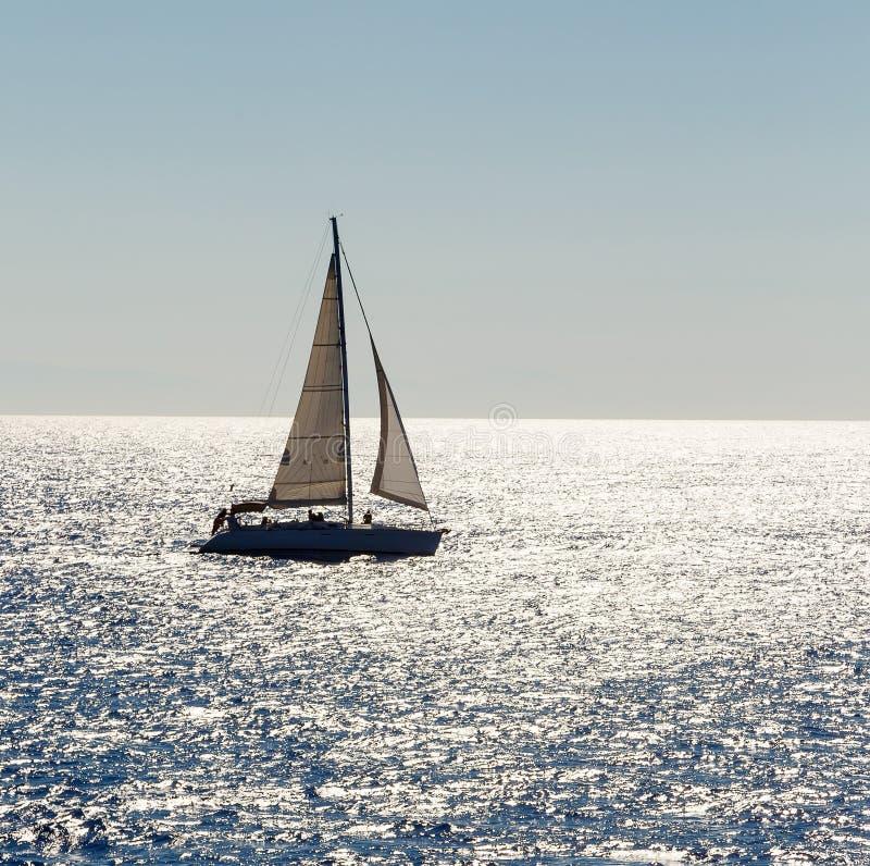 O navio de navigação yachts com as velas brancas no mar aberto fotografia de stock