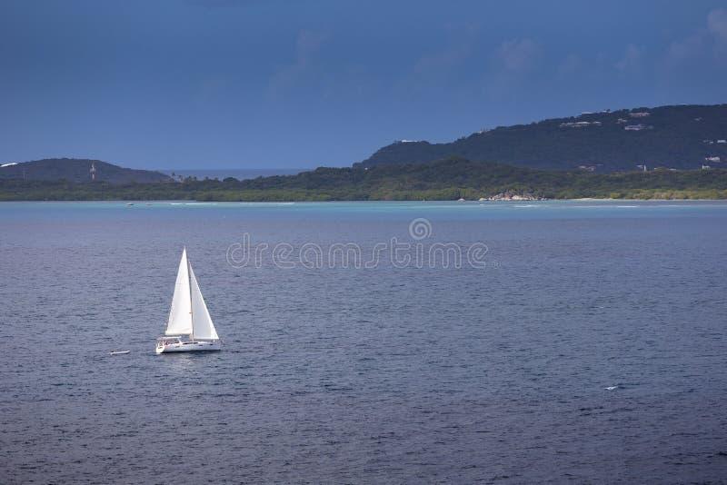 O navio de navigação yachts com a ilha em um fundo fotografia de stock