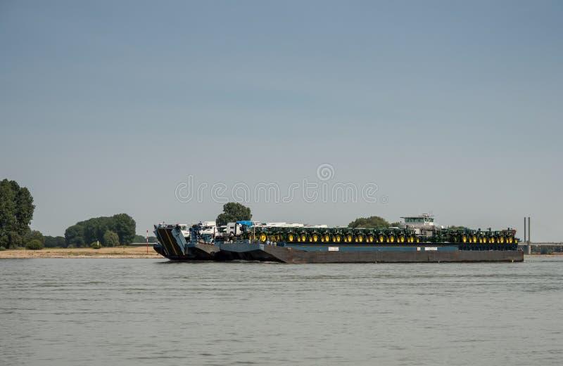 O navio de transporte carregou com os tratores e os caminhões que conduzem o downstrea foto de stock royalty free