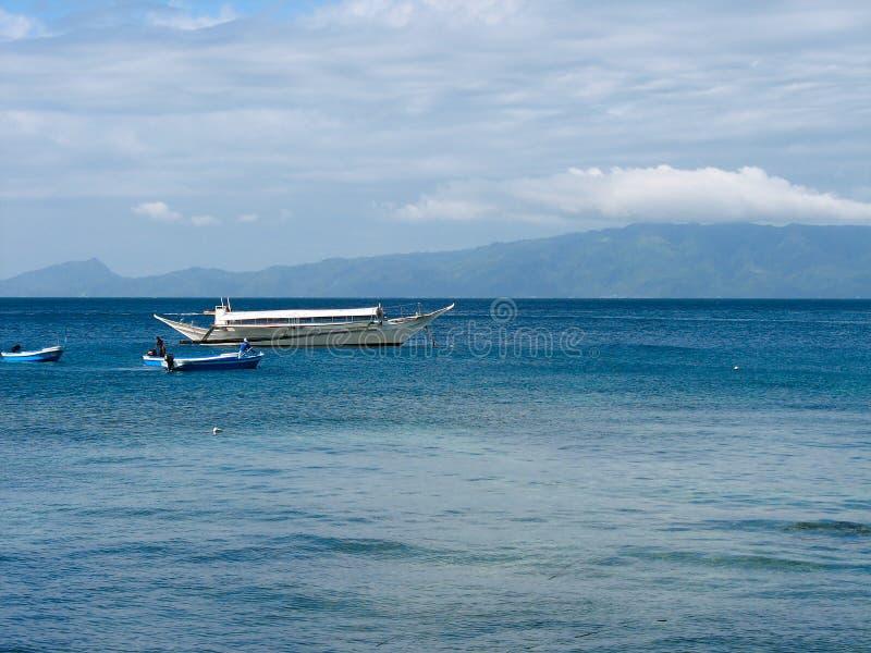 O navio e o barco - o zodíaco está no oceano azul com montanha e nuvens no fundo fotografia de stock