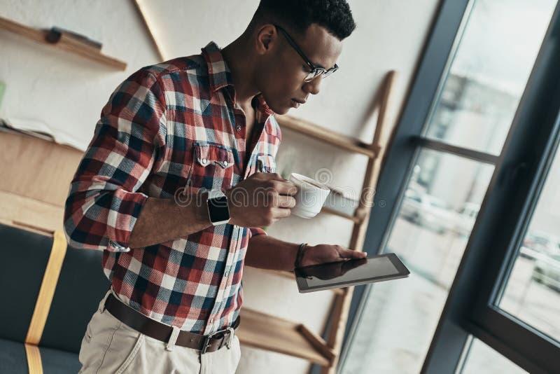 O negócio é sua vida Homem novo considerável que usa a tabuleta digital imagens de stock royalty free