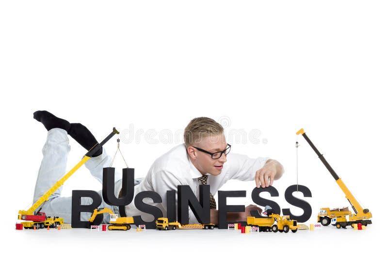 O negócio começa acima: Negócio-w da construção do homem de negócios imagem de stock royalty free